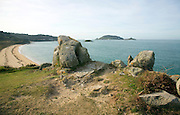 Granite outcrops looking to Bears Beach and island of Jethou, Island of Herm, Channel Islands, Great Britain