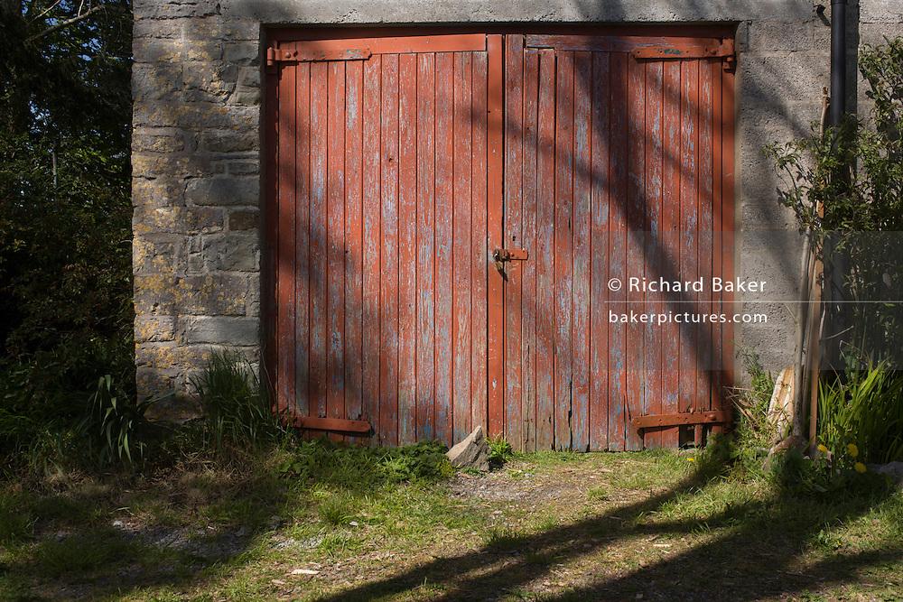 Padlocked peeling garage doors of an old stone garage, in a north Somerset farm.