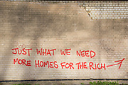 Graffiti protests about the lack of affordable homes outside a site cleared for major housing development in Deptford, South London, UK. Just what we need, more homes for the rich. This protest illustrates the income gap in the UK and the fact that most homes being built in London are unaffordable to people on a normal living wage.