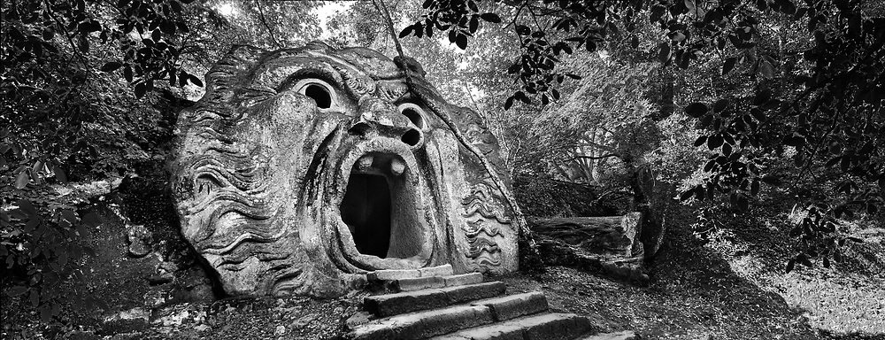 """Sacred Stone - Black and white photo art print of Bomarzo Park of Monsters Sacred Grove by Paul Williams. Sculpture of Orcus (l'orco) king of the underworld, with an incription""""abondon all reason ye who enter here"""", a refernece from Dantes Inferno, commissioned by Piaer Francesco Orsini c. 1513-84, The Renaissance Mannerist statues of the Park of Monsters or The Sacred Wood of Bamarzo, Italy .<br /> <br /> Visit our LANDSCAPE PHOTO ART PRINT COLLECTIONS for more wall art photos to browse https://funkystock.photoshelter.com/gallery-collection/Places-Landscape-Photo-art-Prints-by-Photographer-Paul-Williams/C00001WetsxVxNTo"""