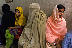 Families wait to be treated at the St. Joseph Hospice day clinic, in Rawalpindi, Pakistan, on Monday Nov. 1, 2006. The hospice was started by Father Francis O'Leary, an Irish missionary, in 1964. Franciscan nuns of the Missionaries of Mary, run the hospice and have a fully trained staff of 26 Pakistani nurses aides and volunteer doctors. The hospice, orphanage and free clinic has 60 beds for resident patients and treats 80-90 out patients daily. All medical services are free of charge to resident patients at St. Joseph's, regardless of the cost, duration or type of treatment required. The hospice is supported solely by donations. (Photo © Jock Fistick)