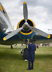 © Licensed to London News Pictures. 16/09/2012. Goodwood, UK . A man looks at a propeller on an a display aircraft. People enjoy the atmosphere at the 2012 Goodwood Revival. The event recreates the glorious days of motor racing and participants are encouraged to dress in period dress. Photo credit : Stephen Simpson/LNP