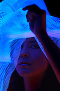 Portrait of a young girl lifting a veil from her hat to get a better look.Black light