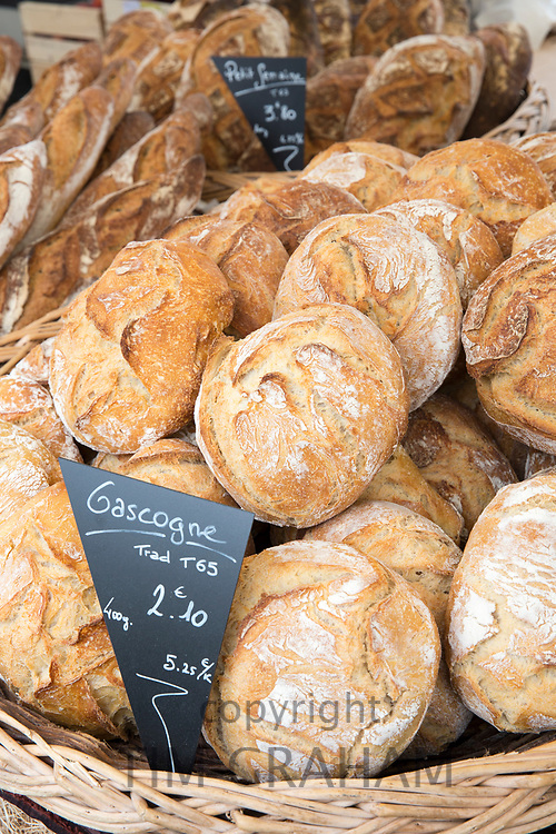French fresh baked Gascogne bread in wicker basket among food on sale at street market Bordeaux, France