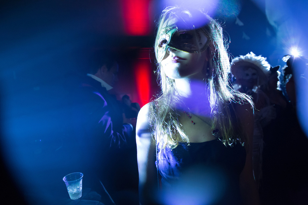A masked woman is caught in the lights.