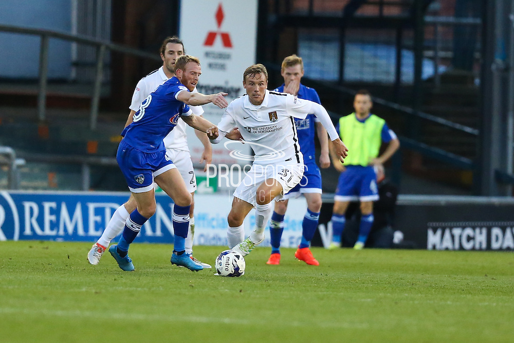 Matthew Taylor of Northampton Town under pressure from Paul Green of Oldham Athletic during the EFL Sky Bet League 1 match between Oldham Athletic and Northampton Town at Boundary Park, Oldham, England on 16 August 2016. Photo by Simon Brady.