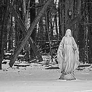 A statue at the Loyola Jesuit Center in Morristown, NJ.  This statue is cutting at the end of a field that is bordered by some woods.  I was shooting in the early morning, just after the blue light.  I was struck by large cross (X) behind her.  The black and white treatment helps to bring out the details as well as the feel of the cold that morning.