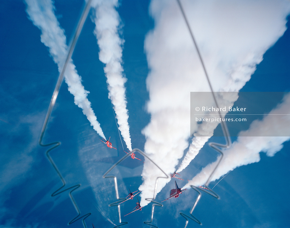Some of the nine Hawk jet aircraft of the elite 'Red Arrows', Britain's prestigious Royal Air Force aerobatic team, perform the 5/4 Split high during an In-Season Practice (ISP) training flight near their base at RAF Scampton. Seen through the explosive Plexiglass cockpit of a tenth plane, we see forward into deep blue sky as two sets of aerobatic pilots steer their machines from a crossover manoeuvre, their organic white smoke pouring from their jet pipes to emphasize their paths through the air. In front of a local crowd at the airfield the team work their way through a 25-minute series of display manoeuvres that are loved by thousands at summer air shows. After some time off, spare days like this are used to hone their manual aerobatic and piloting skills before re-joining the air show circuit. Since 1965 they've flown over 4,000 shows in 52 countries.   .