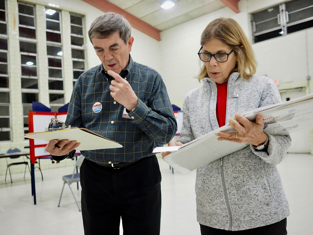 Poll workers review polling information after polls close on Election Day, November 5, 2019