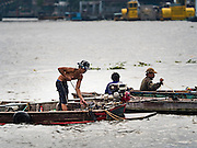 06 OCTOBER 2015 - BANGKOK, THAILAND:    Divers work in two man teams on small boats in the Chao Phraya River. One person stays in the boat while the diver scours the river bottom for anything that can be salvaged and resold. The divers usually work close to shore because the center of the river is a busy commercial waterway with passenger boats and commercial freight barges passing up and down the river all day long. The Chao Phraya is a dangerous river to dive in. It's deep, has large tidal fluctuations, is fast flowing and badly polluted. The divers make money only when they sell something.        PHOTO BY JACK KURTZ