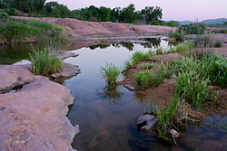 Stock photo of pink granite boulders at sunset lining the Llano River in the Texas Hill Country