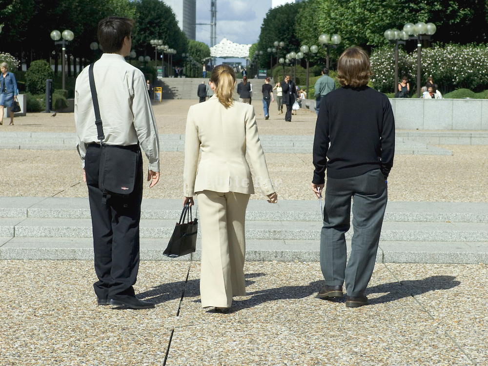 businesswoman in formal dress flanked by two men informalley dressed