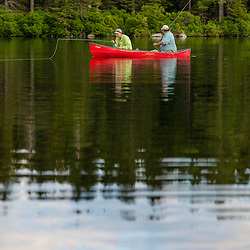 Two men fly-fishing for brook trout from a canoe on Lang Pond in Maine's Northern Forest. Cold Stream watershed, Parlin Pond Township.