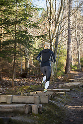 Woman doing exercise at obstacle course on fitness trail in forest