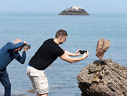 Dunbar, Scotland, UK. 20 April, 2019. Photographers take photos of solitary stone balanced in rock on Eye Cave beach in Dunbar during opening day of the European Stone Stacking Championship 2019.