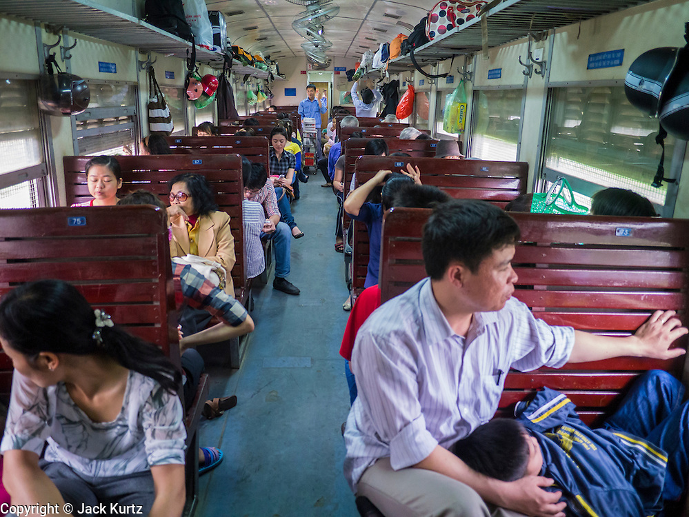 06 APRIL 2012 - HAI PHONG, VIETNAM: A family in a third class car on the Hanoi and Hai Phong Express. The train has three classes: 1st, 2nd and 3rd. Tickets cost between $3(US) and $2(US) one way. The Hanoi to Hai Phong Express Train runs several times a day between Long Bien Station in Hanoi and the Hai Phong Station. Hanoi is the capital of Vietnam and Hai Phong is the 4th largest city in Vietnam. Hai Phong is the principal industrial port in the northern part of Vietnam. It was heavily bombed and mined during the American War (what Americans call the Vietnam War).   PHOTO BY JACK KURTZ