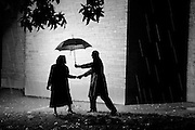 A man invites  a woman to share his umbrella as they walk outside in the rain.
