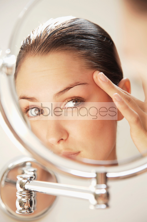 Close up of a young woman looking into round mirror checking her face