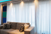 Detail of sofa in modern apartment with a big window and frames