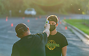 Before practice begins, Pecatonica-Argyle High School football coach Larry Green takes the temperatures of all the football players. Keegan Brunker stands as the coach clears him for practice. (Photo © Andy Manis)