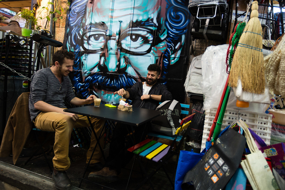 Israelis drink coffee in front of a graffiti depicting film director Steven Spielberg which was painted over a closed shutter next to a home utility store, at the Mahane Yehuda Market, often called 'The Shuk' in Jerusalem, Israel, on February 24, 2016.