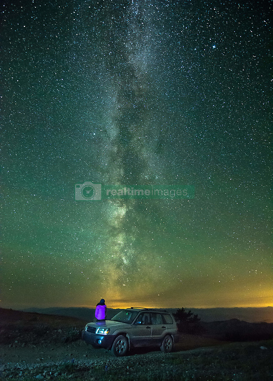 July 26, 2017 - Person sitting on car, looking at view of milky way, rear view, Nickel Plate Provincial Park, Penticton, British Columbia, Canada (Credit Image: © Preserved Light Photography/Image Source via ZUMA Press)