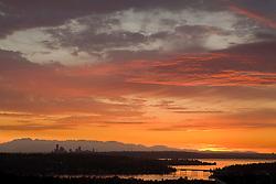 North America, United States, Washington. Lake Washington, Mercer Island, Seattle skyline, and Olympic mountains viewed from Bellevue at sunset.