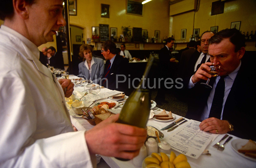 A businessman sips a chilled glass of white wine to accompany a dish of seafood in Sweetings in the City of London. A waiter waits for the man's verdict before filling the glass then tending his order from the table menu. Associates talk discreetly in the background in this very traditional bar in the heart of the capital's financial district, near St Paul's Cathedral. Sweetings Restaurant first opened in 1889 and has carried out serving lunch ever since. Sweetings prides itself on offering a wide variety of English sustainable fish, from wild fresh Scottish Salmon, usually the first fish of the season, to the native oysters from West Mersea on the Essex coast.