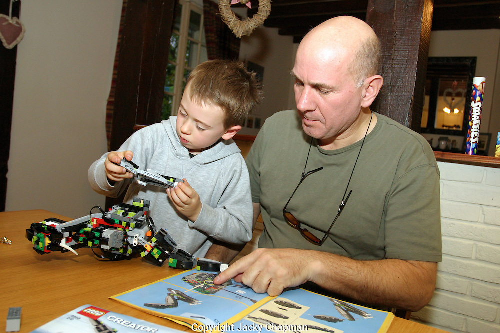 Father and son building model Lego car together