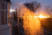 Warm, orange light from a late, flaring sunset shines through condensation in a window that overlooks a residential street and tall trees in south London, on 12th February 2021, in London, England.