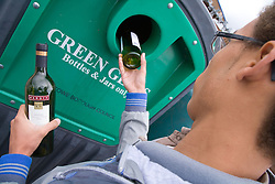 Teenage boy putting bottles in a green glass and jars into a recycling bank,