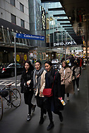 Pedestrians on Little Bourke Street walk past a sign for Caledonian Lane in the Central Business District of Melbourne, Australia
