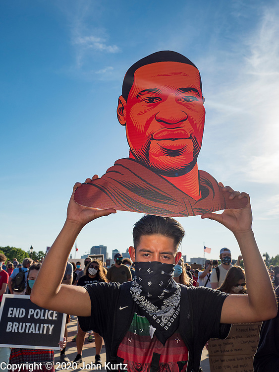 01 JUNE 2020 - DES MOINES, IOWA: A man holds a cutout of George Floyd during a prayer in front of the Iowa State Capitol Monday. About 1,000 people gathered in front of the Iowa State Capitol in Des Moines Monday evening for a rally calling for racial justice. The rally was one week after George Floyd, an unarmed black man, was killed by a Minneapolis police officer who knelt on Floyd's back for more than eight minutes. There were protests  in Des Moines all weekend against Floyd's killing. There was some violence and some people have been arrested but the protests in Des Moines haven't been as serious as protests in other cities.          PHOTO BY JACK KURTZ