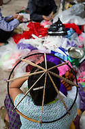 """A Vietnamese woman sits with a conical hat frame on her head, Chuong Village, Ha Tay Province, Vietnam, Southeast Asia, 2013. This handicraft village specializes in the fabrication of the conical hat, known as """"non"""" in Vietnamese."""