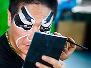 26 AUGUST 2018 - GEORGE TOWN, PENANG, MALAYSIA: A performer puts on his make up before going on stage for a Hokkien style Chinese opera on the Lim Jetty in George Town for the Hungry Ghost Festival. The opera troupe came to George Town from Fujian province in China. The Hungry Ghost Festival is a traditional Buddhist and Taoist festival held in Chinese communities throughout Asia. The Ghost Festival, also called Ghost Day, is on the 15th night of the seventh month (25 August in 2018). During the Hungry Ghost Festival, the deceased are believed to visit the living. In many Chinese communities, there are Chinese operas and puppet shows and elaborate banquets are staged to appease the ghosts.     PHOTO BY JACK KURTZ