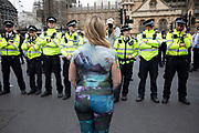 Climate change activist from the Extinction Rebellion group with her body painted stands in front of police lines at Parliament Square in protest that the government is not doing enough to avoid catastrophic climate change and to demand the government take radical action to save the planet, on 23rd April 2019 in London, England, United Kingdom. Extinction Rebellion is a climate change group started in 2018 and has gained a huge following of people committed to peaceful protests.