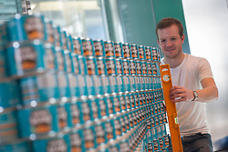 © licensed to London News Pictures. London, UK 24/06/2012. Nick Weston carefully positioning a can to a wall of Heinz Beans, which has 3,444 cans. Teams of leading architects, designers and engineers competing today as they sculptures from cans of food at One Canada Square Shopping Centre today. Photo credit: Tolga Akmen/LNP