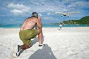 Baie de St. Jean. Small airplanes starting and landing at St. Barth's tiny airport next to the shore are always a thrilling view. Here a tourist takes a souvenir photo with his wife.