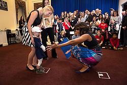 First Lady Michelle Obama reaches out to a child during a visit with children from Children's Miracle Network Hospitals, in the Eisenhower Executive Office Building of the White House, Nov. 10, 2014. (Official White House Photo by Lawrence Jackson)<br /> <br /> This official White House photograph is being made available only for publication by news organizations and/or for personal use printing by the subject(s) of the photograph. The photograph may not be manipulated in any way and may not be used in commercial or political materials, advertisements, emails, products, promotions that in any way suggests approval or endorsement of the President, the First Family, or the White House.