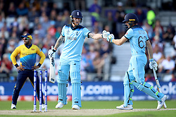 England's Ben Stokes (centre) and Jos Buttler bump fists during the ICC Cricket World Cup group stage match at Headingley, Leeds.