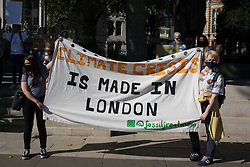 Young people stand alongside a Fossil Free London banner in Parliament Square during a Global Climate Strike to demand intersectional climate justice on 24th September 2021 in London, United Kingdom. The Global Climate Strike was organised to highlight the detrimental influences through colonialism, imperialism and exploitation of the Global North on MAPA (Most Affected Peoples and Areas), which have contributed to them now experiencing the worst impacts of the climate crisis, and to call on the Global North to pay reparations to MAPA.