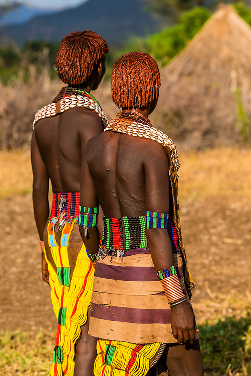 Two Hamer tribe women walking and holding hands, Omo Valley, Ethiopia.