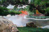 Orange bridge over a small lake leading to the Golden pagoda, The Pavilion of Absolute Perfection, Nan Lian Garden, Kowloon (Diamond Hill), Hong Kong, August 2008. The Nan Lian garden is built on a classical design of the Tang Dynasty, with rocks, ponds, and plantings.   Photo: Peter Llewellyn