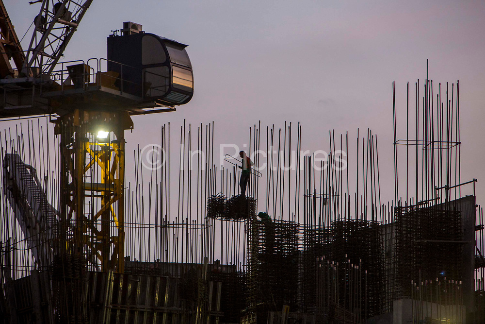 Construction workers work without safety gear on top of Garden Towers under construction at dusk on East Street, Makati, Metro Manila, Philippines.
