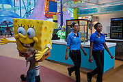 Tiffany Whitehead,(right) a student and part-time ride supervisor at the Mall of America amusement park, goes on a routine check of the mall with a colleague in Bloomington, Minnesota. (From the book What I Eat: Around the World in 80 Diets.) The Mall of America is the largest among some 50,000 shopping malls in the United States. In addition to a huge amusement park, it houses over 500 stores, 26 fast-food outlets, 37 specialty food stores, and 19 sit-down restaurants, and employs more than 11,000 year-round employees. In excess of 40 million people visit the mall annually, and more than half a billion have visited since it opened in 1992. Tiffany's job involves a lot of walking. Her main beat is the amusement park area, where she responds to radio calls regarding stalled rides and lost children and answers visitors' questions. MODEL RELEASED.