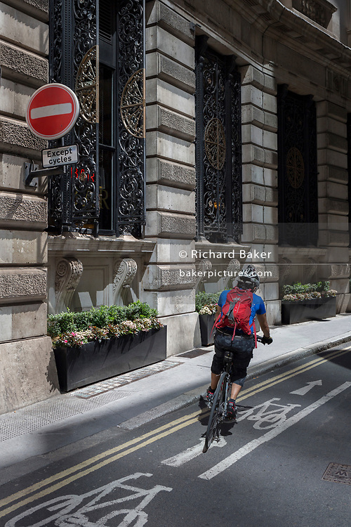 A cyclist turns onto a cycle lane on Finch Street, a narrow medieval-era lane in the City of London, the capital's historic financial district, on 2nd August 2018, in London, England.