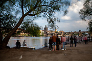 """Crowds at """"Kampa"""" park feeding swans and photographing each other with Charles Bridge in the background."""