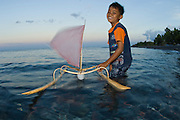Young boy in Tulamben, Bali, Indonesia playing in the surf with a model or toy jukung, the traditional fishing vessel in Bali.