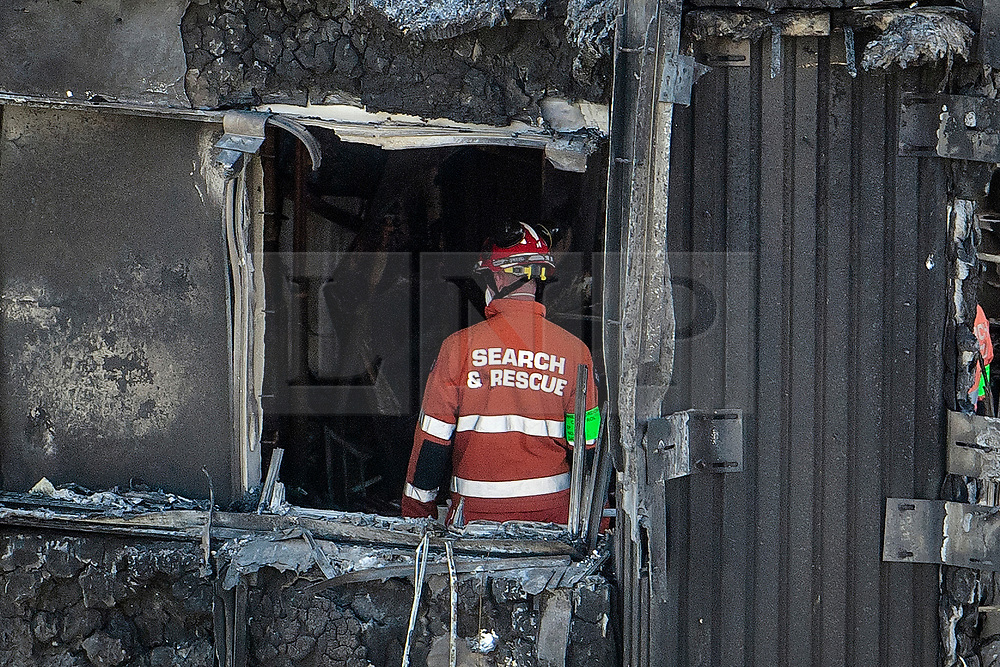 © Licensed to London News Pictures. 17/06/2017. London, UK. Members of a fire investigation team inspect damage caused by a fire at the Grenfell tower block in west London earlier this week. The blaze engulfed the 27-storey building killing 12 - with 34 people still in hospital, 18 of whom are in critical condition. The fire brigade say that they don't expect to find anyone else alive. Photo credit: Ben Cawthra/LNP