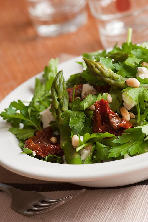 Fresh salad made of coriander, asparagus, feta and tomatoes